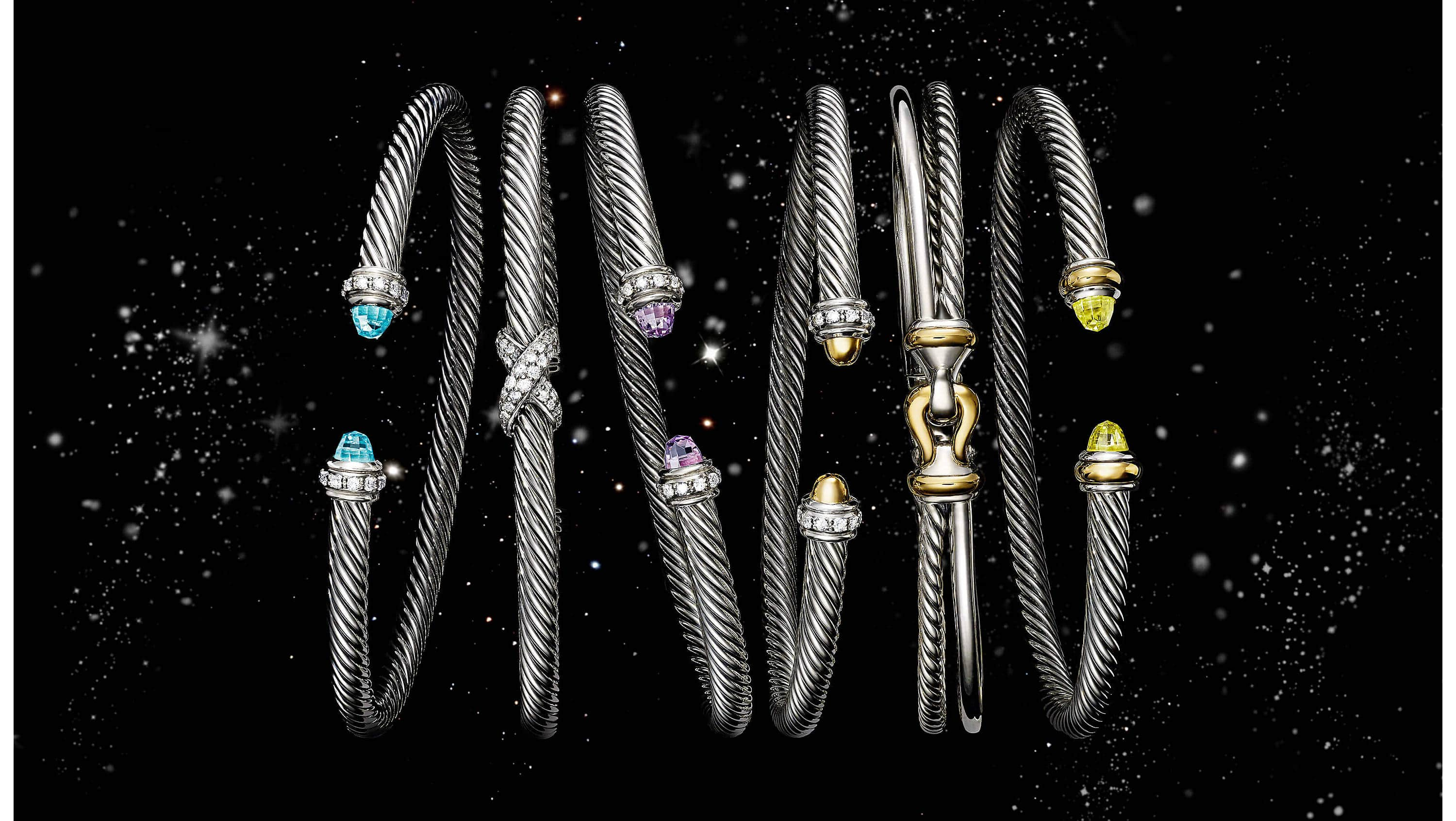 A color photo shows six David Yurman women's bracelets from the Cable, Buckle and X collections floating in a starry night sky. The jewelry is crafted from sterling silver with or without pavé diamonds, colored gemstones and 18K yellow gold accents.