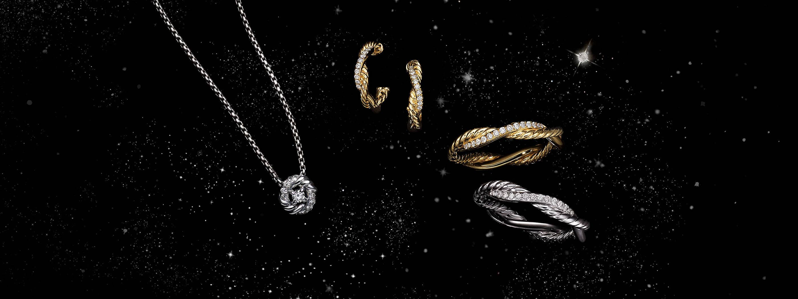 A color photo shows a pendant necklace floating next to a pair of hoop earrings and two band rings from David Yurman women's Infinity Collection in front of a starry night sky. The jewelry is crafted from strands of sterling silver or 18K yellow gold Cable entwined with pavé diamonds.