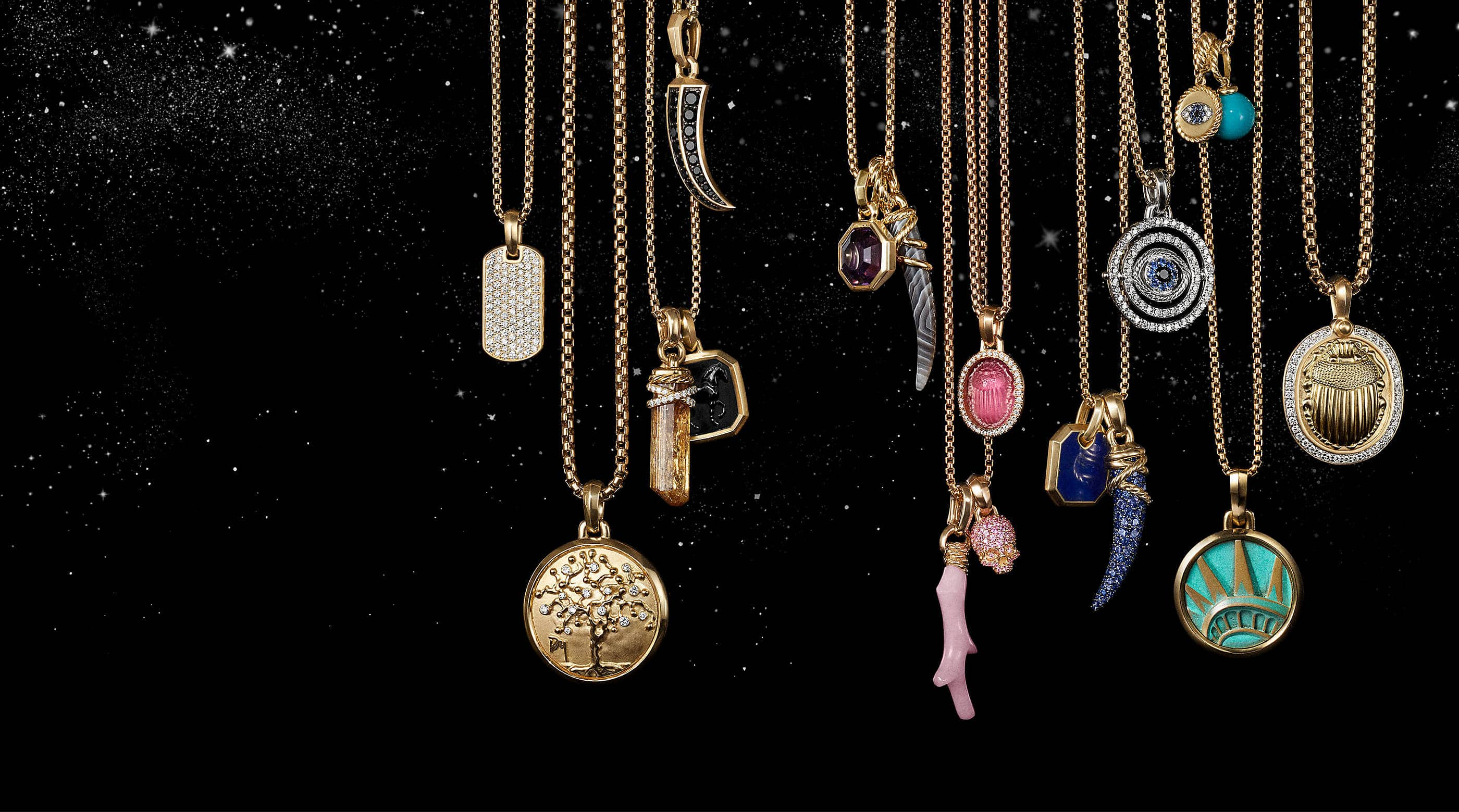 A color photograph shows 17 David Yurman amulet pendants hanging from a horizontal row of chain necklaces in front of a starry night sky. The women's jewelry is crafted from 18K yellow gold or sterling silver with or without pavé diamonds and an array of colored gemstones. The pendants come in various shapes such as a tag, branch of coral, horn, dagger, or skull or depict a multitude of images such as a tree of life, scarab and the Statue of Liberty's crown.