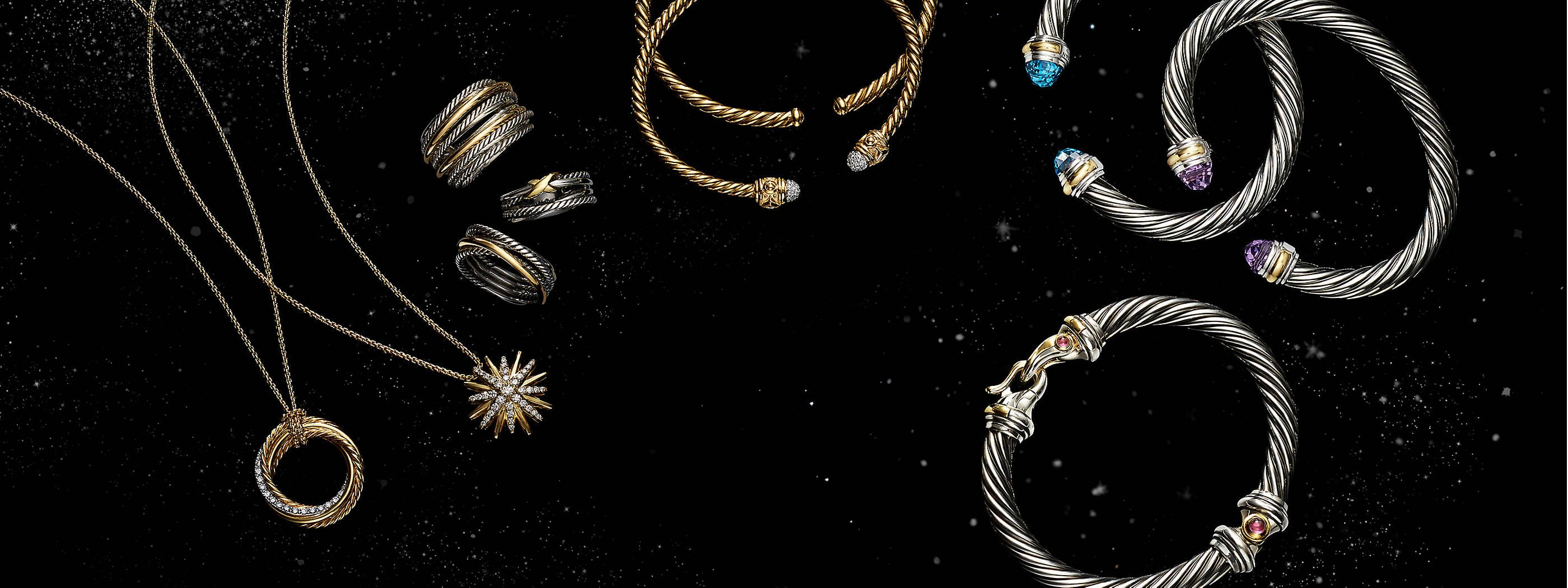 A color photo shows an overhead shot of a horizontal stack of five David Yurman bracelets from the Helena, Stax, Pure Form and Pavéflex collections placed atop a purple stained-glass panel by Brian Clarke with illuminated sections. Three of the women's bracelets are crafted from 18K yellow gold with pavé white diamond accents. Two of the women's bracelets are crafted from 18K yellow gold.