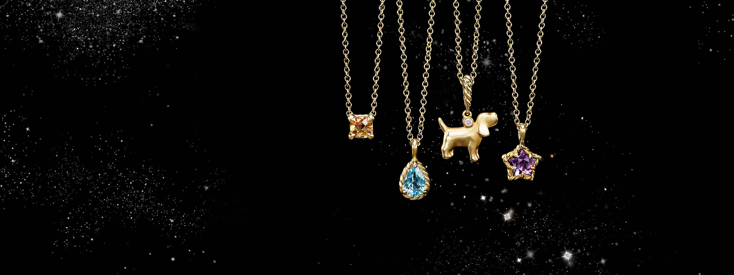 A color photograph shows four David Yurman kids' pendant necklaces hanging in front of a starry night sky. The kids' jewelry is crafted from 18K yellow with or without a cushion-cut citrine, teardrop-shaped blue topaz, dog charm with a white diamond and star-shaped amethyst.