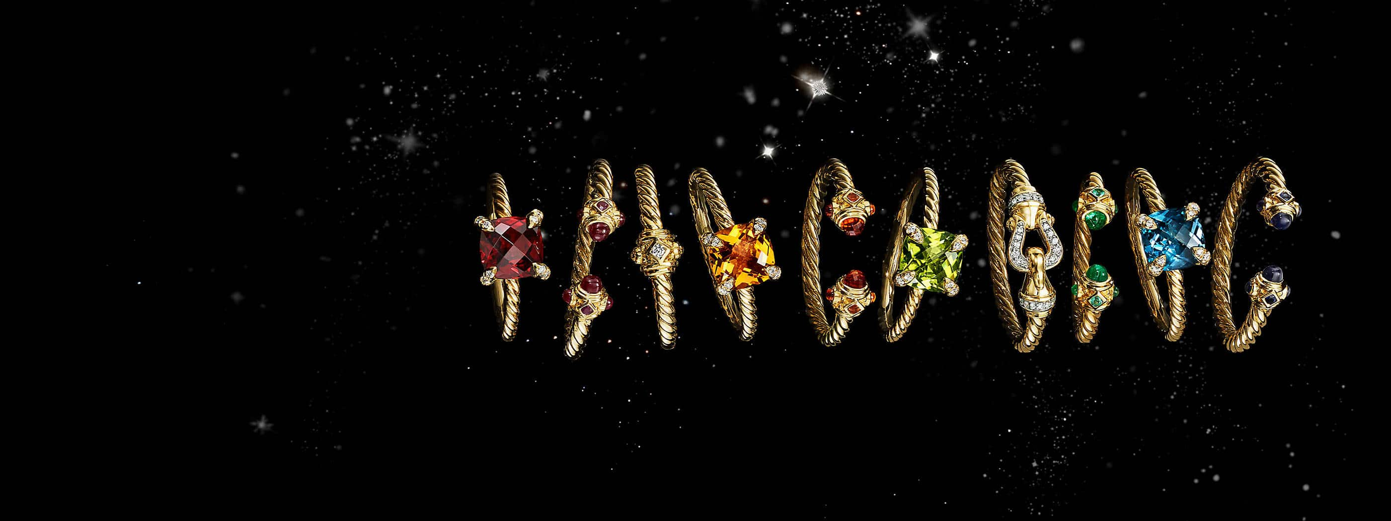 A color photo shows a horizontal row of ten David Yurman women's rings from the Renaissance, Châtelaine, Buckle and Venetian Quatrefoil collections floating in front of a starry night sky. The jewelry is crafted from 18K yellow gold with or without pavé diamonds and colored gemstones.