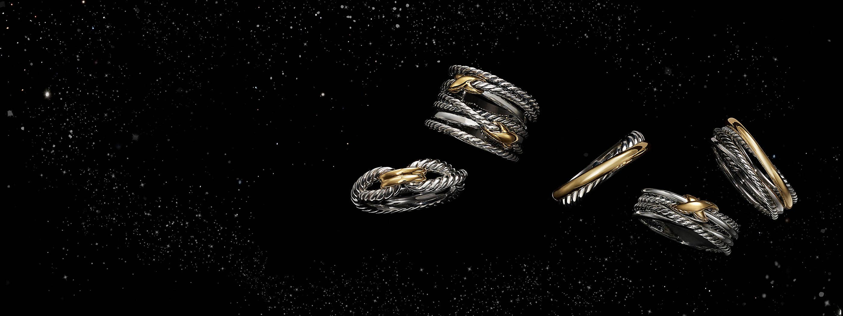 A color photograph shows five David Yurman women's rings from the Crossover and X collections floating in front of a starry night sky. The jewelry is crafted from sterling silver with 18K yellow gold accents.