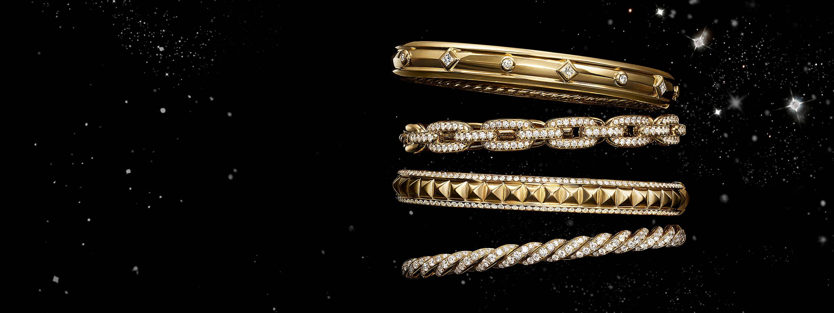 A color photo shows a vertical stack of four David Yurman women's bracelets from the Modern Renaissance, Stax and Pavéflex collections floating in front of a starry night sky. The jewelry is crafted from 18K yellow gold with diamonds.