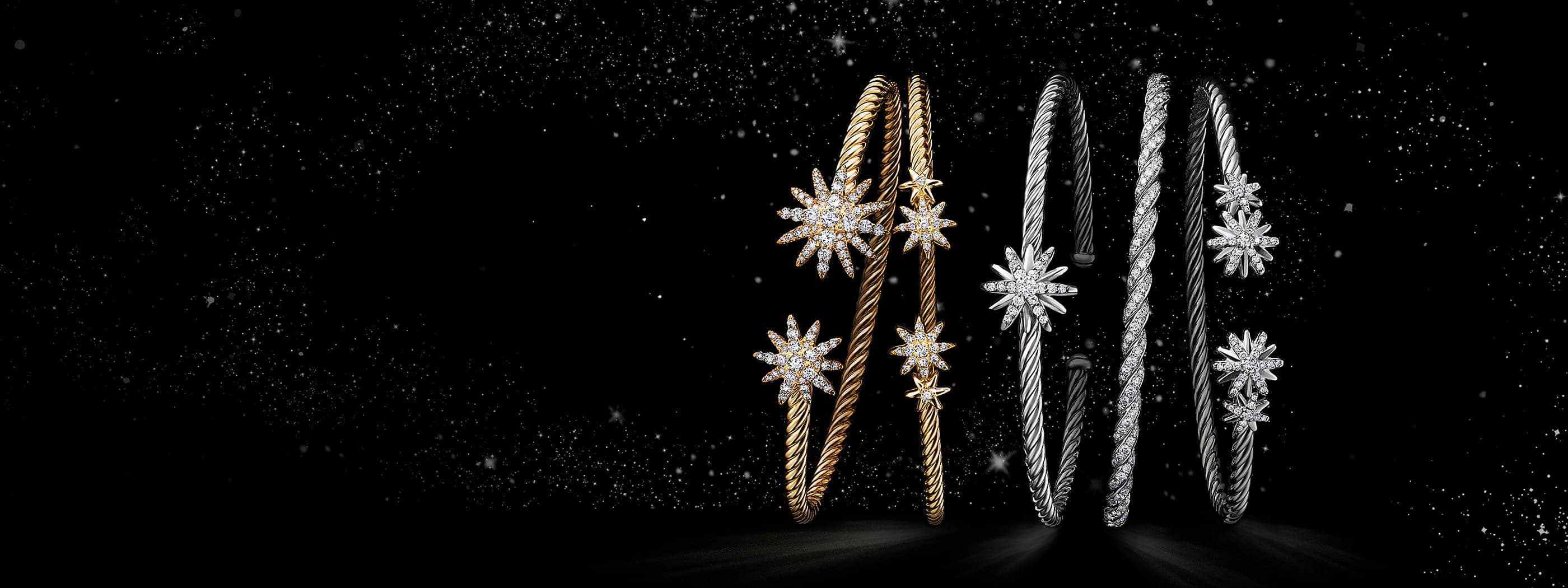 A color photograph shows a horizontal stack of five David Yurman women's bracelets from the Starburst and Pavéflex collections floating atop a white cloud in a starry night sky. The jewelry is crafted from 18K white or yellow gold with pavé diamonds or sterling silver with pavé diamonds.