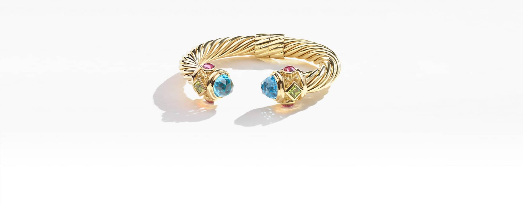 A color photo shows a cable Renaissance bracelet laying down in 18K yellow gold with blue topaz, peridot and pink tourmaline