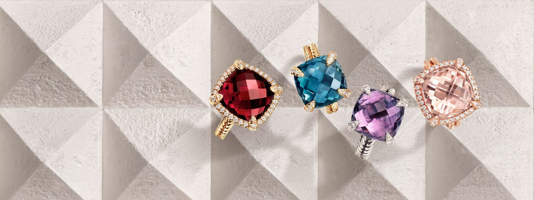 An overhead shot of a vertical stack of David Yurman Châtelaine rings placed atop a  beige-hued stone surface with pyramid-shaped protrusions. The women's jewelry is crafted from 18K yellow or rose gold or sterling silver with morganite, amethyst, blue topaz or garnet center stones surrounded by bezels or prongs set with pavé white diamonds.