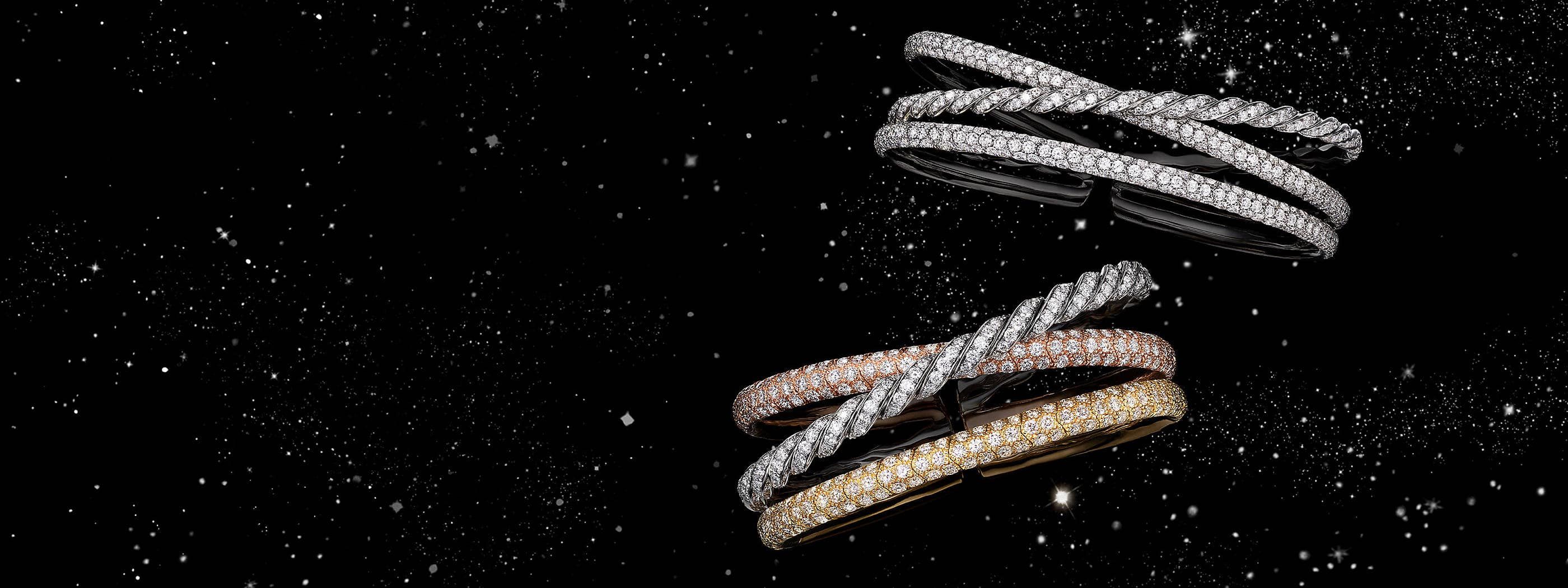 A color photograph shows two David Yurman women's Pavéflex three-row bracelets floating in front of a starry night sky. The bracelets are crafted from 18K white gold with pavé diamonds or 18K yellow, white and rose gold with pavé diamonds.