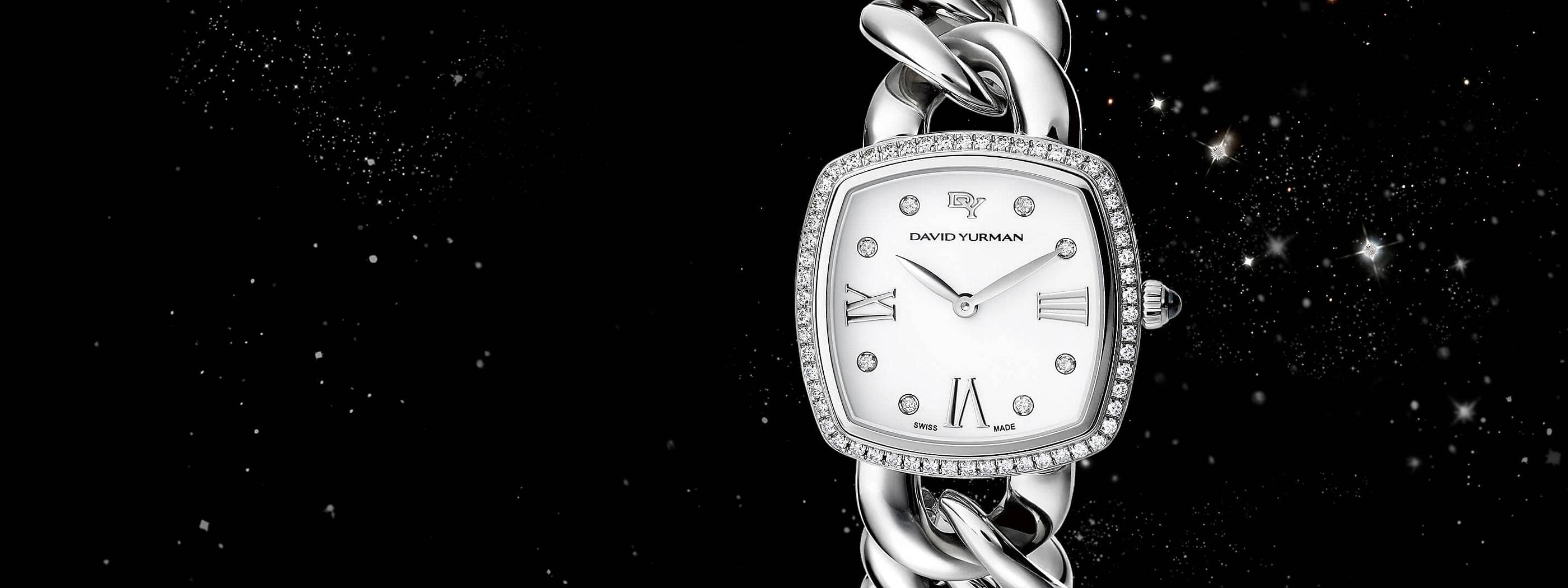 A color photograph shows a close-up shot of a David Yurman women's Albion bracelet watch floating in front of a starry night sky. It is crafted from stainless steel with pavé diamonds.