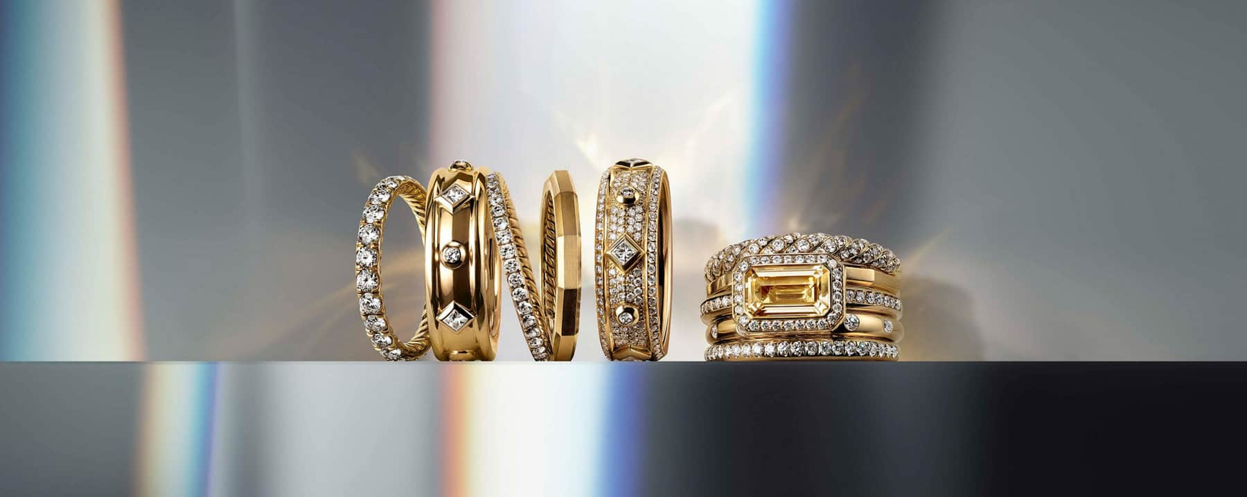 A color photo shows six David Yurman rings from the DY Eden, Modern Renaissance and Stax collections lined up in a horizontal row on a clean surface. The jewelry is crafted from 18K yellow gold with diamonds and with or without a Champagne citrine. In the background are reflections of rainbow-hued light.