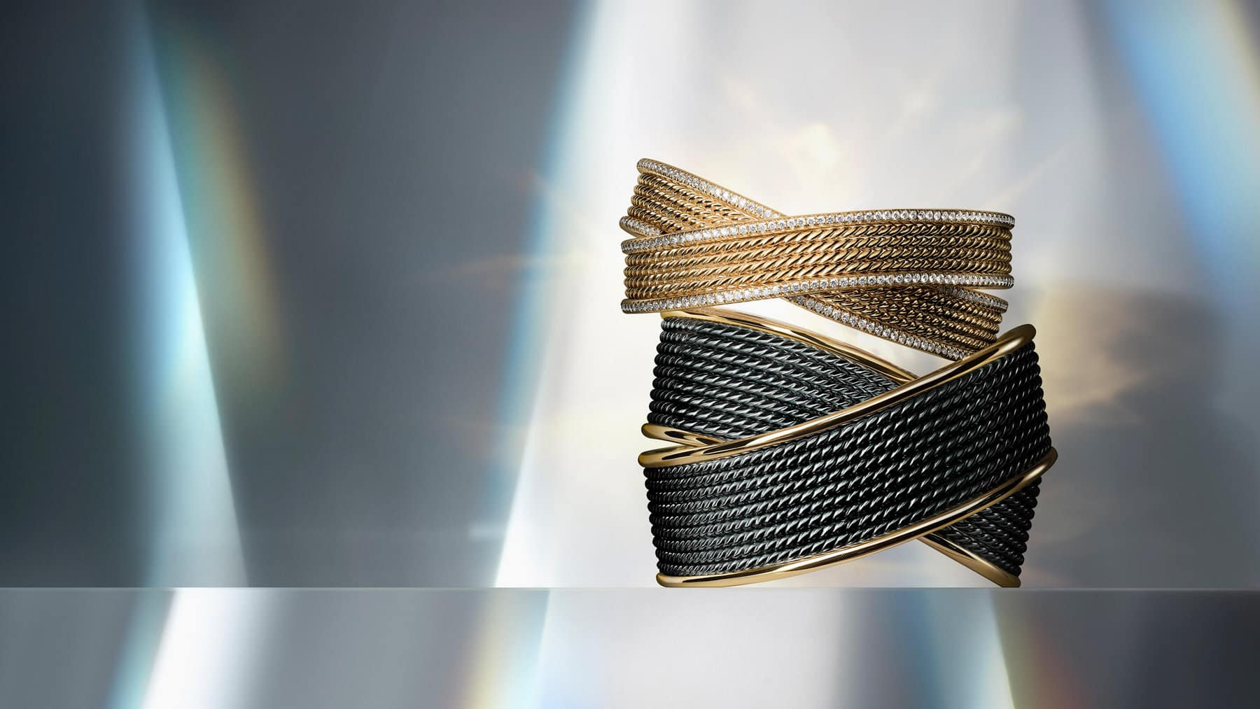 A color photo shows two David Yurman crossover cuff bracelets stacked on top of each other from the DY Origami collection. The top cuff is crafted from 18K yellow gold with pavé diamond accents. The bottom cuff is crafted from blackened sterling silver with 18K yellow gold accents. In the background are reflections of rainbow-hued light.