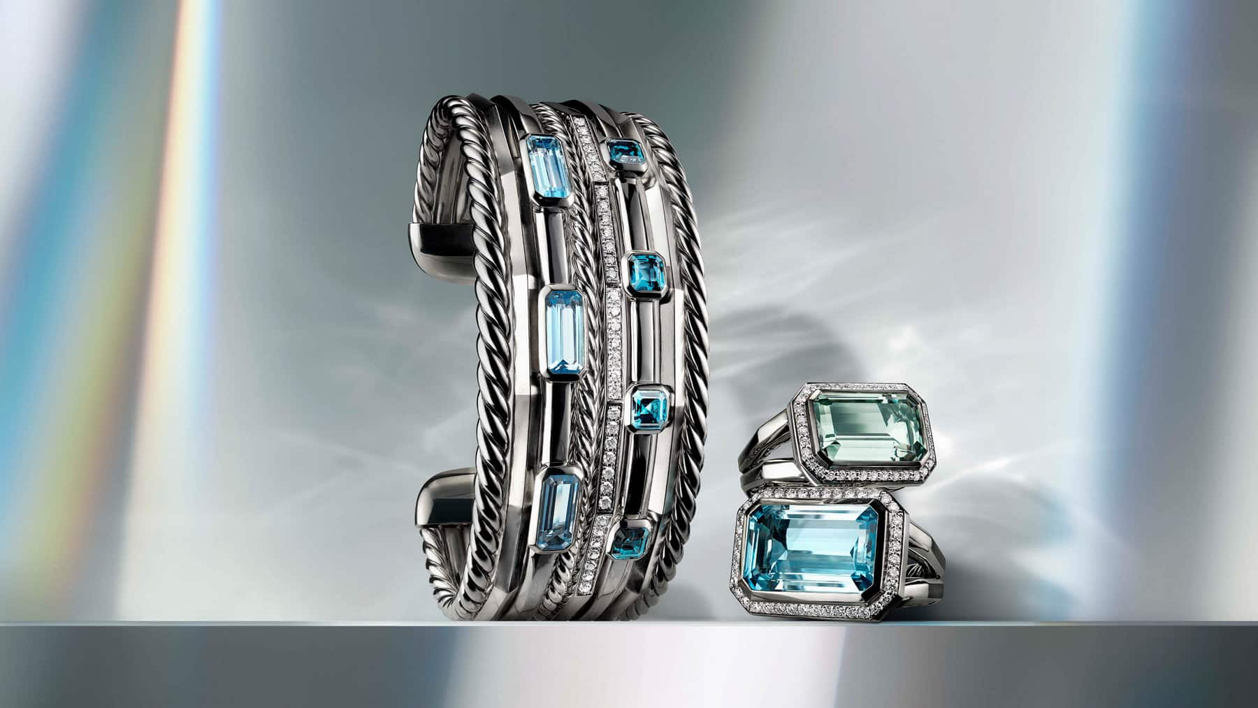 A color photo shows a David Yurman multi-row Stax cuff standing on its side next to a stack of two Novella rings.  The jewelry is crafted from sterling silver with emerald-cut blue topaz and prasiolite gemstones and pavé diamond accents. In the background are reflections of rainbow-hued light.