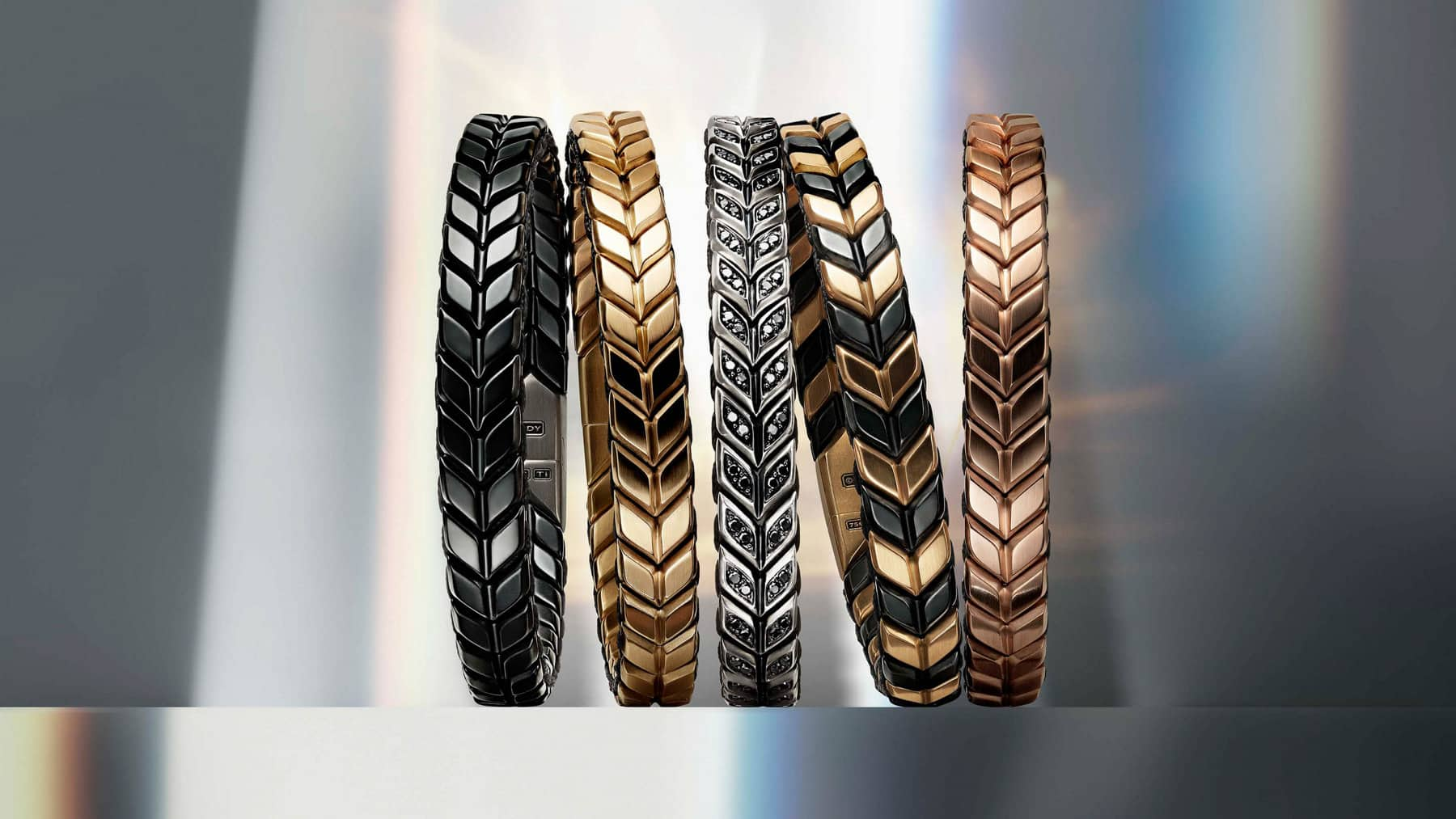 A color photo shows five David Yurman Chevron bracelets in a horizontal stack. The jewelry is crafted from black titanium, 18K yellow gold, sterling silver with pavé black diamonds, black titanium with 18K yellow gold, and 18K rose gold. In the background are reflections of rainbow-hued light.