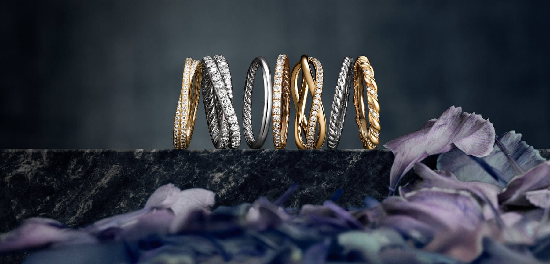 A color photograph shows a row of seven David Yurman wedding bands from the DY Crossover, DY Eden, DY Wisteria and DY Unity collections atop a dark, marbled stone surface with a dark background and flowers in the foreground. Each is crafted from 18K yellow or rose gold, or platinum, with or without diamonds.