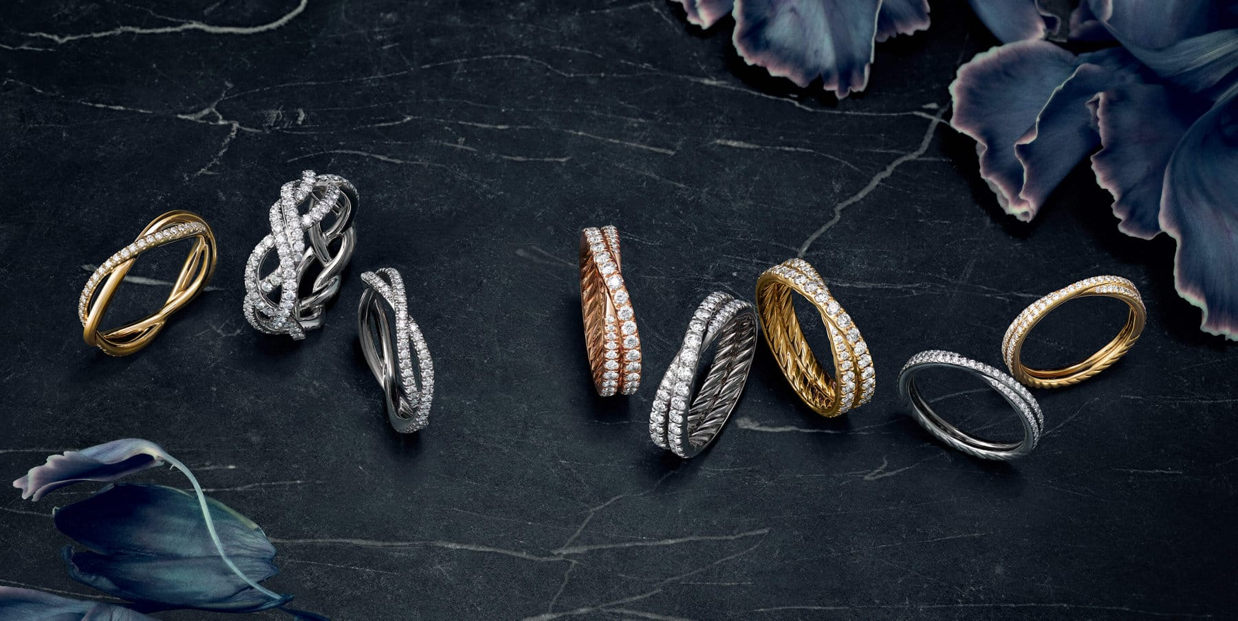 A color photograph shows eight David Yurman women's wedding bands from the DY Lanai, DY Wisteria and DY Crossover   collections. The rings sit atop a dark, marbled stone surface with flowers petals on either side.