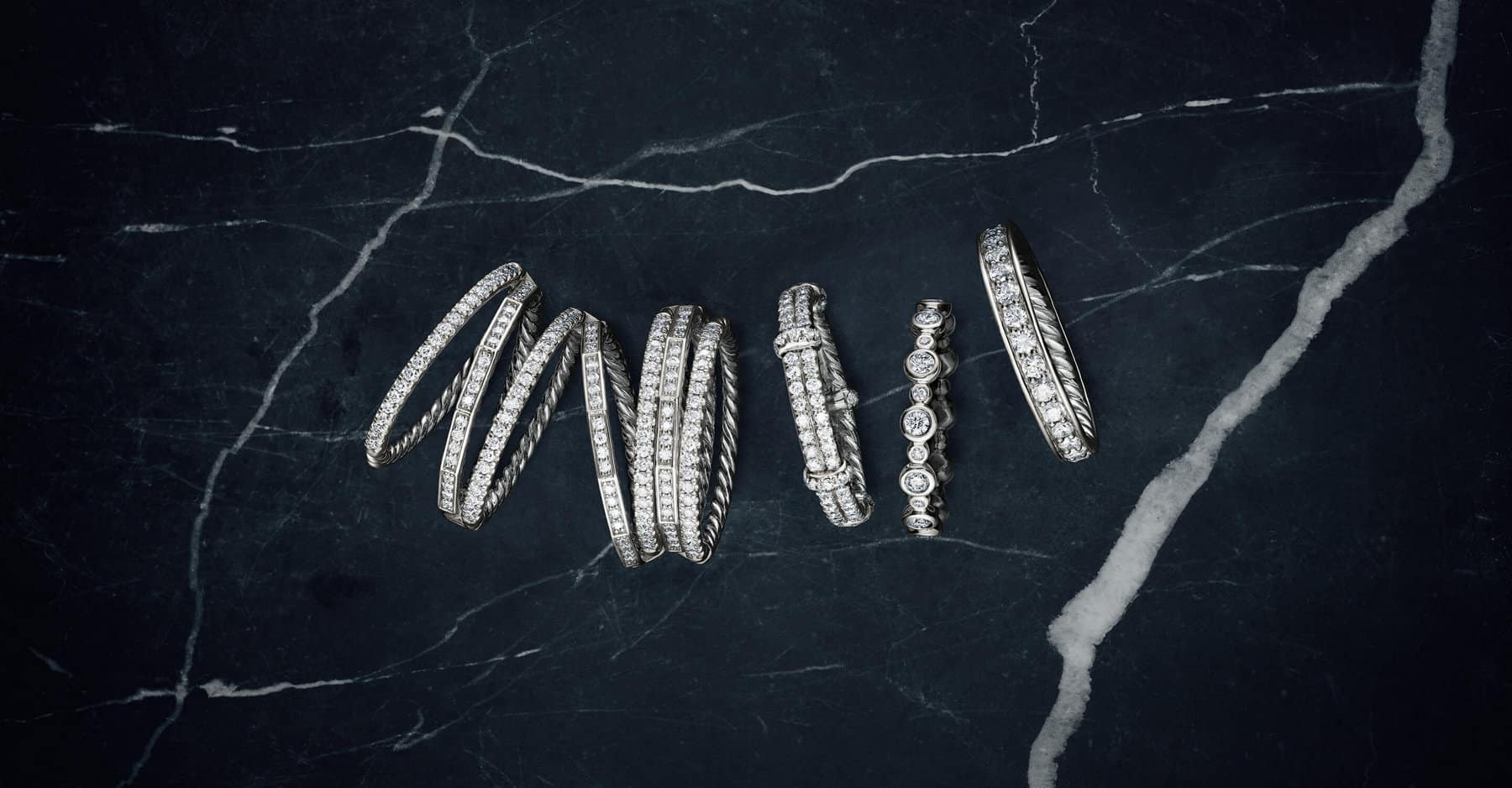 A color photo shows a row of David Yurman wedding bands from the Stax, DY Astor, DY Starlight and DY Eden collections atop a dark, marbled stone surface. Each ring is crafted in platinum with diamonds.