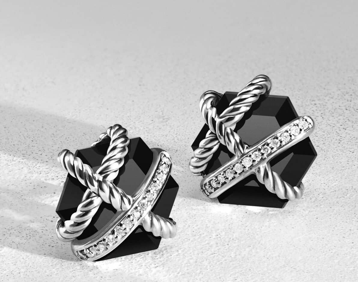 A color photo shows a pair of David Yurman Cable Wrap earrings standing upright and casting long shadows on a white surface. The jewelry is crafted from faceted black onyx with sterling silver and pavé white diamonds