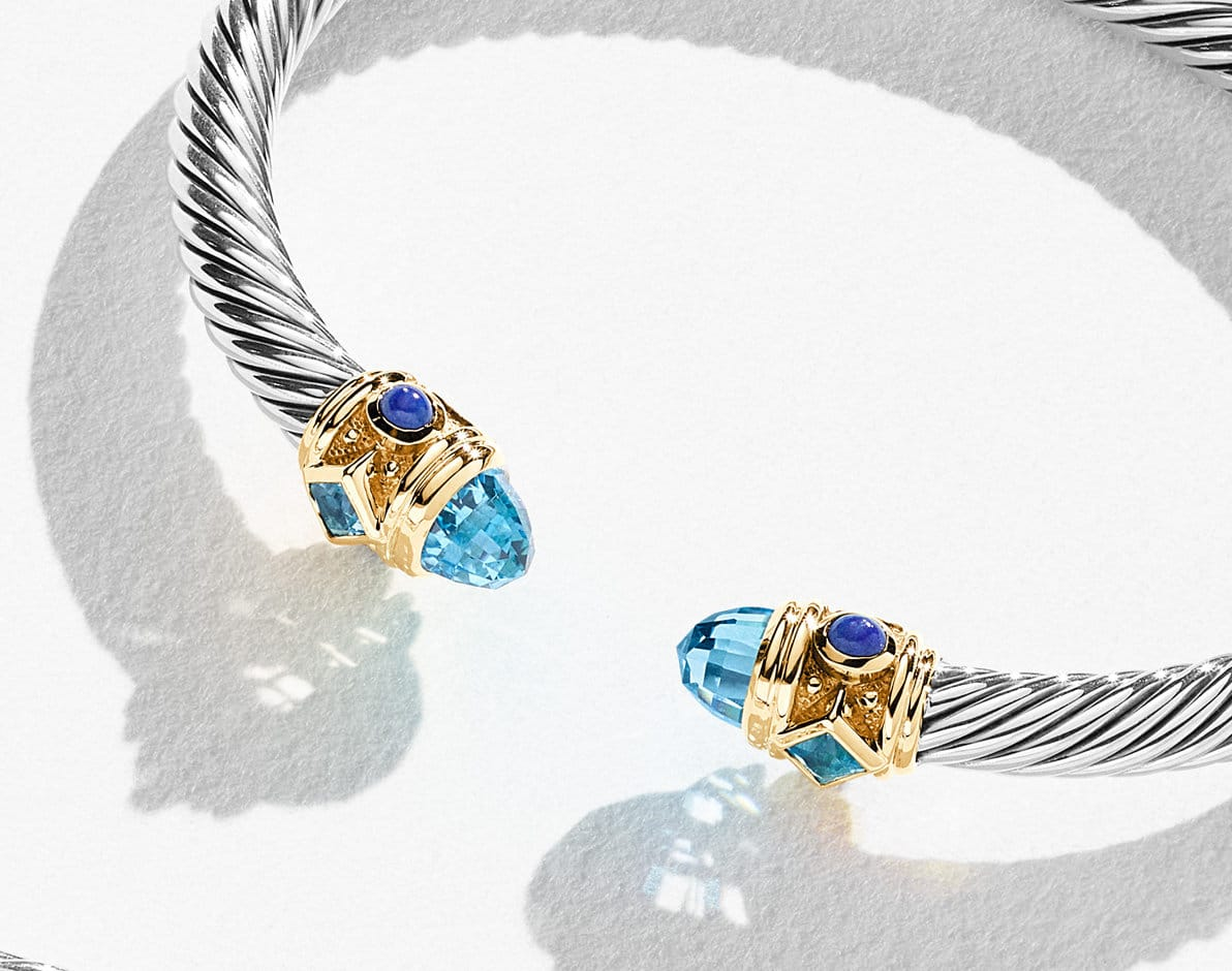A color photo shows a David Yurman Renaissance bracelet on top of and casting long shadows on a white surface. The jewelry is crafted from sterling silver with 14K yellow gold, faceted blue topaz and cabochon lapis lazuli.