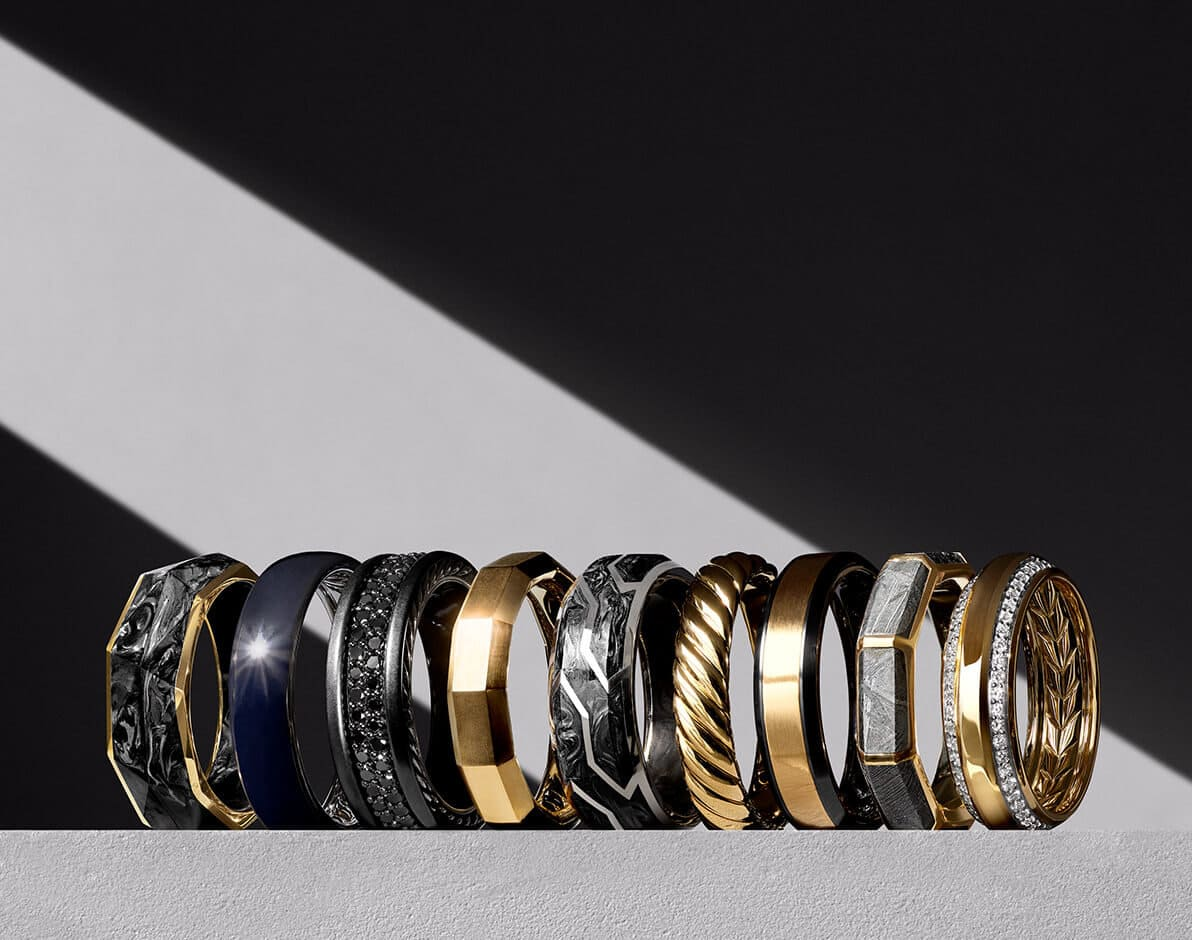 A color photo shows nine David Yurman men's band rings standing upright in a horizontal row on top of a block of textured light grey stone. Diagonal rays of light cover most of the stone and the center of the background behind the rings, with shadows framing the light. From are a Faceted band in 18K yellow gold with forged carbon, a DY Classic band in sterling silver with black titanium, a Streamline band in grey titanium with pavé black diamonds, a Faceted band in 18K yellow gold, a Forged Carbon band in sterling silver, a Cable band in 18K yellow gold, a Beveled band in black titanium with 18K yellow gold, a Faceted band in 18K yellow gold with meteorite and a Beveled band in 18K yellow gold with pavé white diamonds.