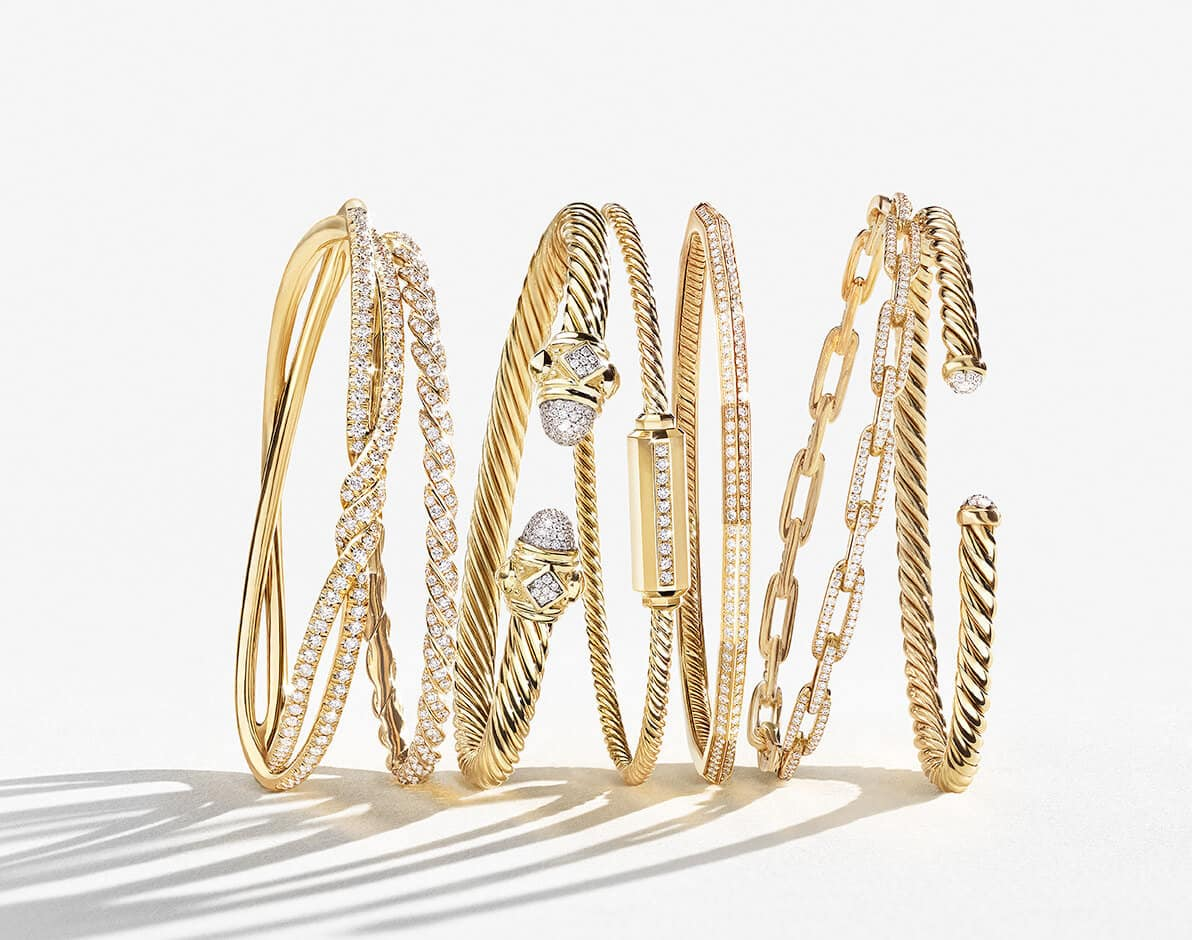 A color photo shows horizontal stack of David Yurman bracelets standing upright and leaning against each other while casting long shadows on a white surface. The jewelry is from the Continuance, Paveflex, Cable, Barrels, Faceted and Stax collections and is crafted from 18K yellow gold with pavé white diamonds.
