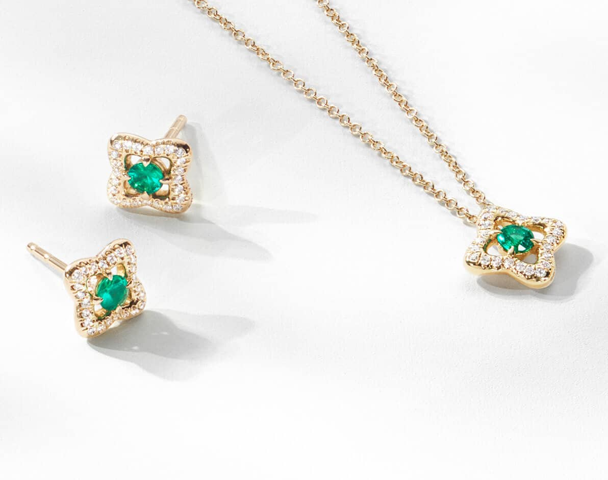 A color photo shows a pair of David Yurman stud earrings and a David Yurman necklace laying in a group and casting long shadows on top of a white surface. The jewelry is from the Venetian Quatrefoil Collection and is crafted from 18K yellow gold, faceted emeralds and pavé white diamonds.