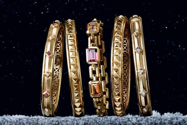 A color photo shows five David Yurman bracelets from the Renaissance and Novella collections placed in a horizontal stack. The women's jewelry is crafted from 18K yellow gold with or without white diamonds, rubies, garnet or citrine, and photographed atop a snow-dusted stone ledge at night under a starry sky.