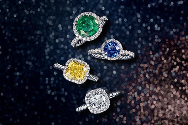 A color photograph shows an overhead shot of four DY Capri® engagement rings arranged in a group atop a black glittery surface. The rings are crafted from platinum with pavé white diamonds surrounding a DY Signature Cut® yellow diamond or white, an emerald or a sapphire center stone.