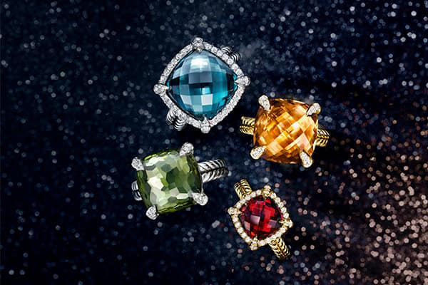 An overhead shot of David Yurman Châtelaine rings for women shows the jewelry arranged in a circle atop a black glittery background. The jewelry is crafted in sterling silver or 18K yellow gold with center stones of Hampton blue topaz, citrine, garnet or lemon citrine over hematine with pavé white diamond bezels or prongs.