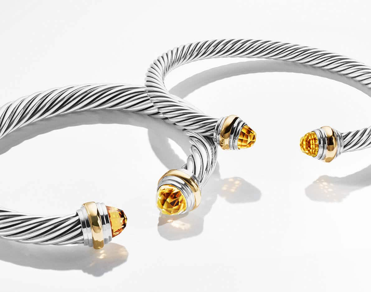 A color photo shows two David Yurman Cable bracelets leaning one on top of the other and casting long shadows on top of a white surface. The jewelry is crafted from sterling silver with faceted citrine endcaps and 18K gold details.