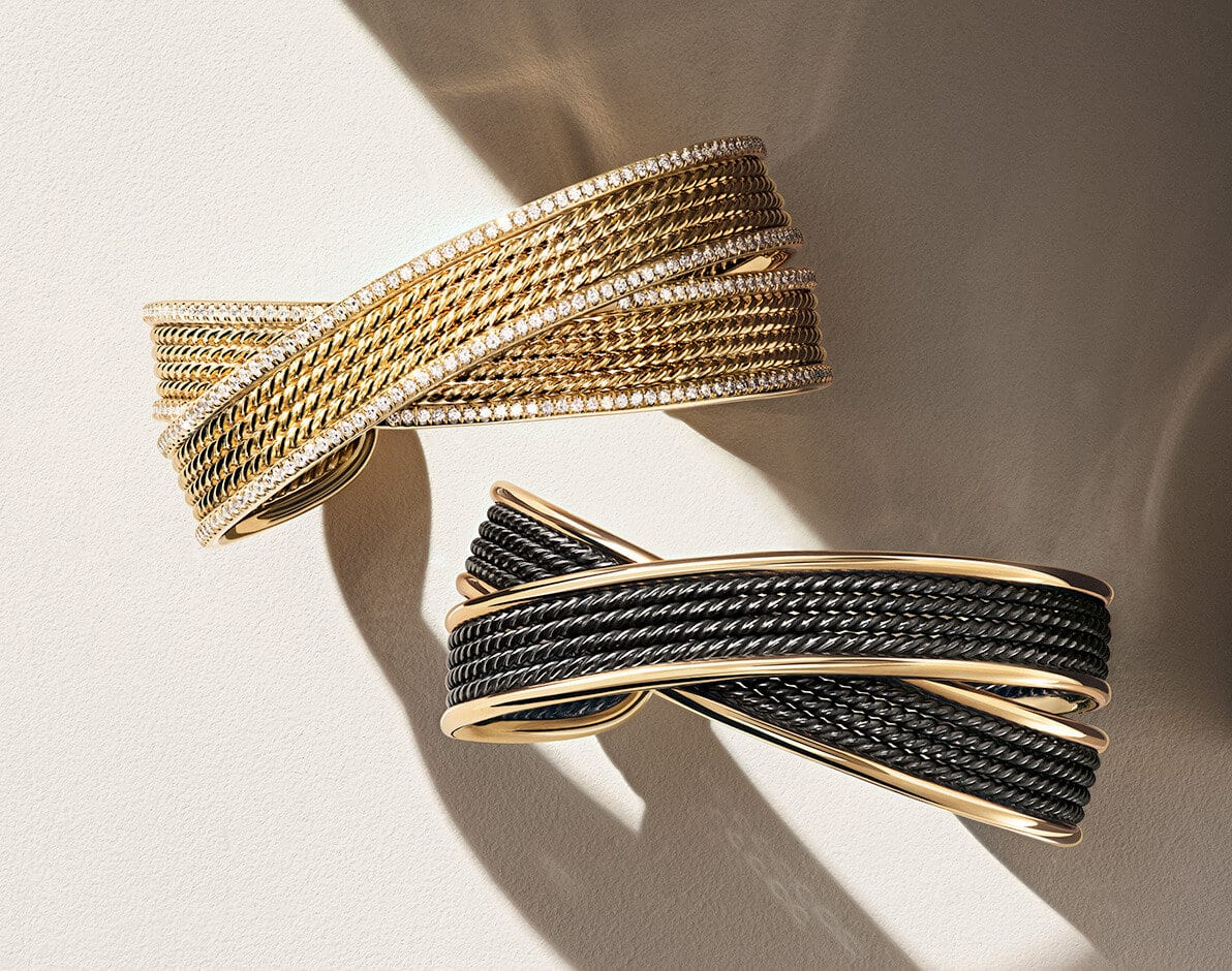 A color photo shows two David Yurman DY Origami bracelets standing upright next to each other and casting long shadows on a beige stone bathed in light and shadow. From top, the jewelry is crafted from 18K yellow gold with pavé white diamonds or blackened silver with 18K yellow gold.