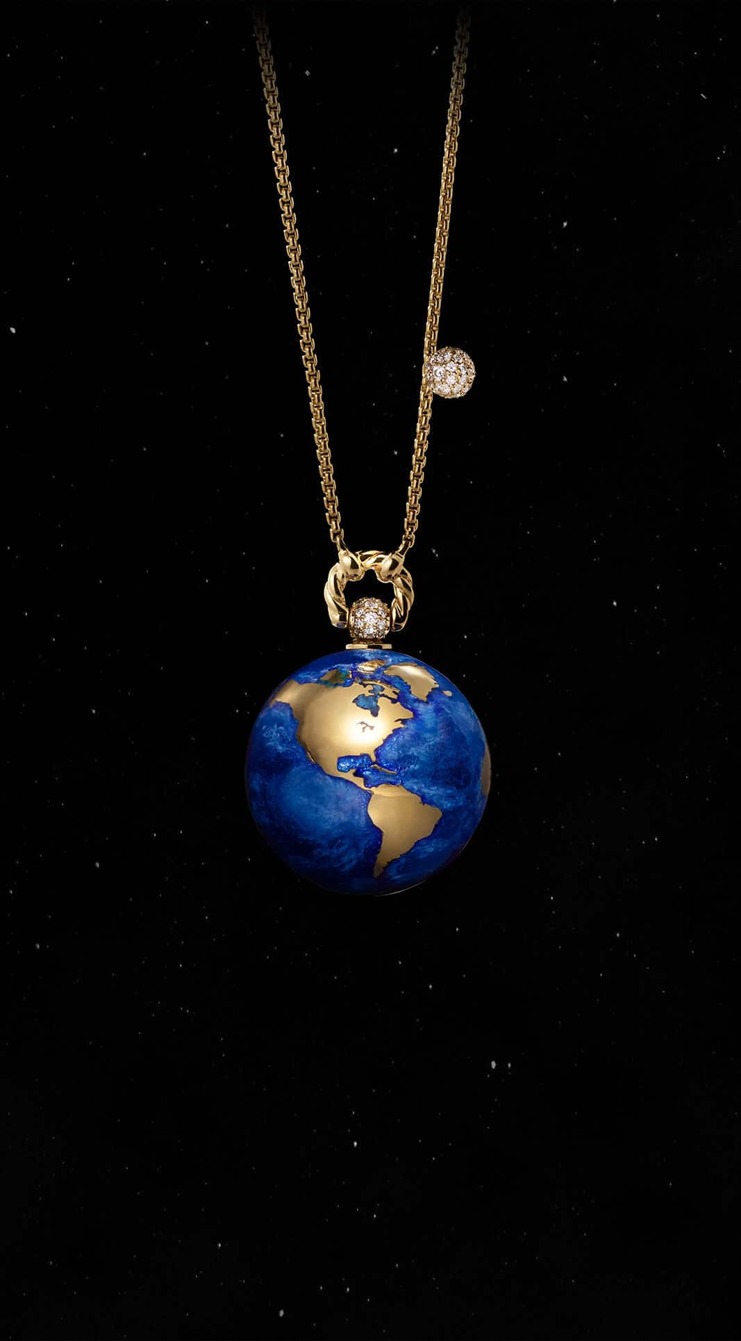 A color photo shows the David Yurman Solari Planet Earth pendant necklace in front of a starry night sky. The pendant is crafted from 18K yellow gold with silver foil, vitreous enamel and white diamonds.