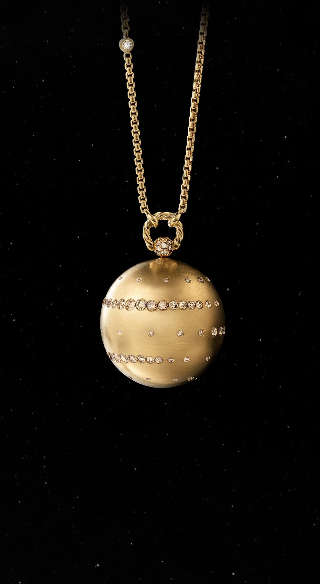 A color photo shows the David Yurman Solari Planet Jupiter pendant necklace in front of a starry night sky. The pendant is crafted from 18K yellow gold with cognac diamonds.