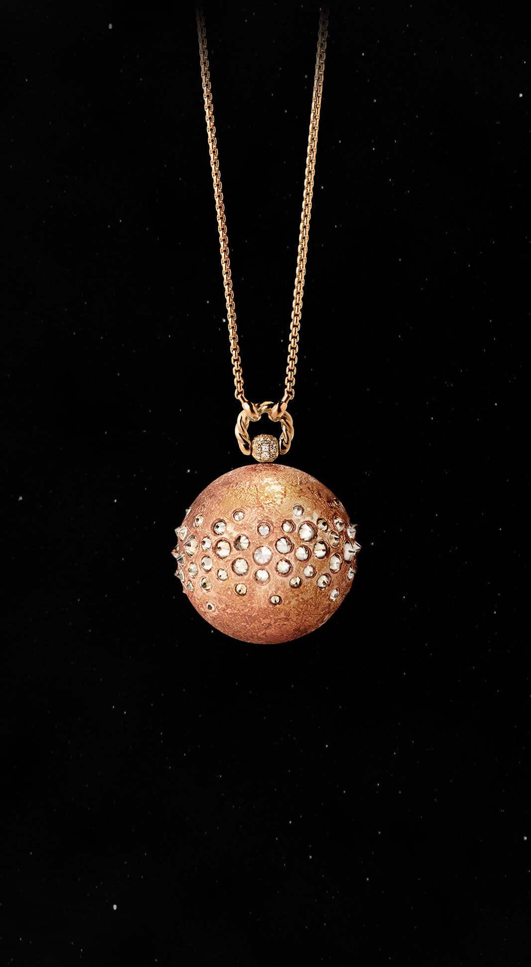 A color photo shows the David Yurman Solari Planet Mars pendant necklace in front of a starry night sky. The pendant is crafted from 18K rose gold with cognac diamonds.
