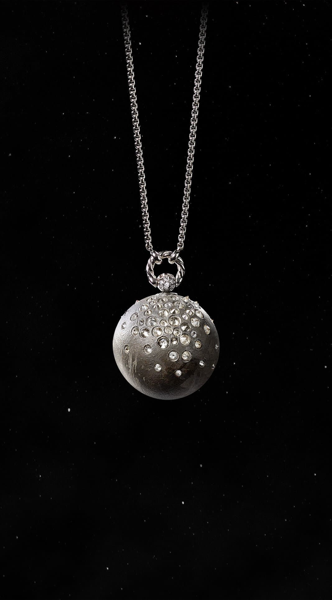 A color photo shows the David Yurman Solari Planet Mercury pendant necklace in front of a starry night sky. The pendant is crafted from meteorite with 18K white gold and grey and white diamonds.