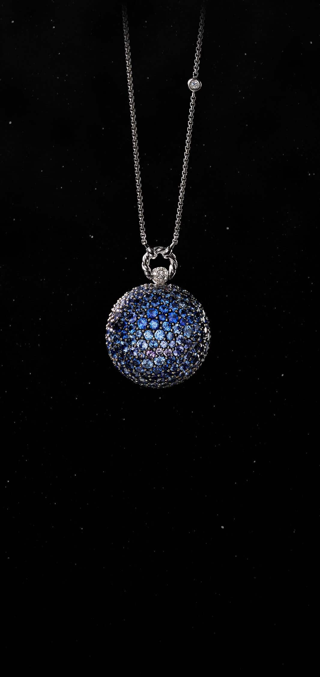 A color photo shows the David Yurman Solari Planet Neptune pendant necklace in front of a starry night sky. The pendant is crafted from rhodium-plated 18K white gold with blue and purple sapphires.