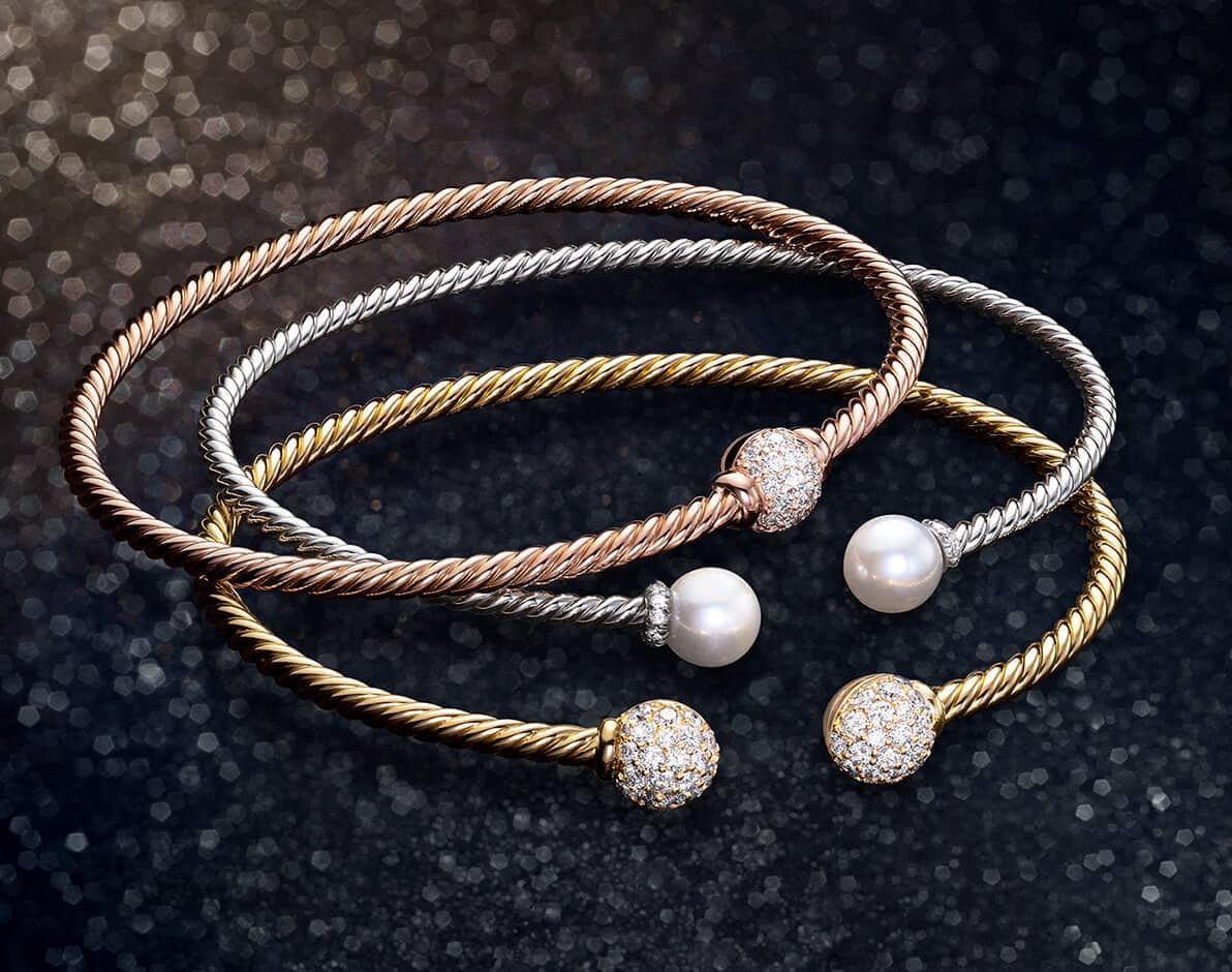 A color photo shows three David Yurman Solari women's bracelets stacked on top of each other on a glittery black background. The jewelry is crafted from 18K rose, white or yellow gold with cultured freshwater pearls or white diamond-covered orbs.