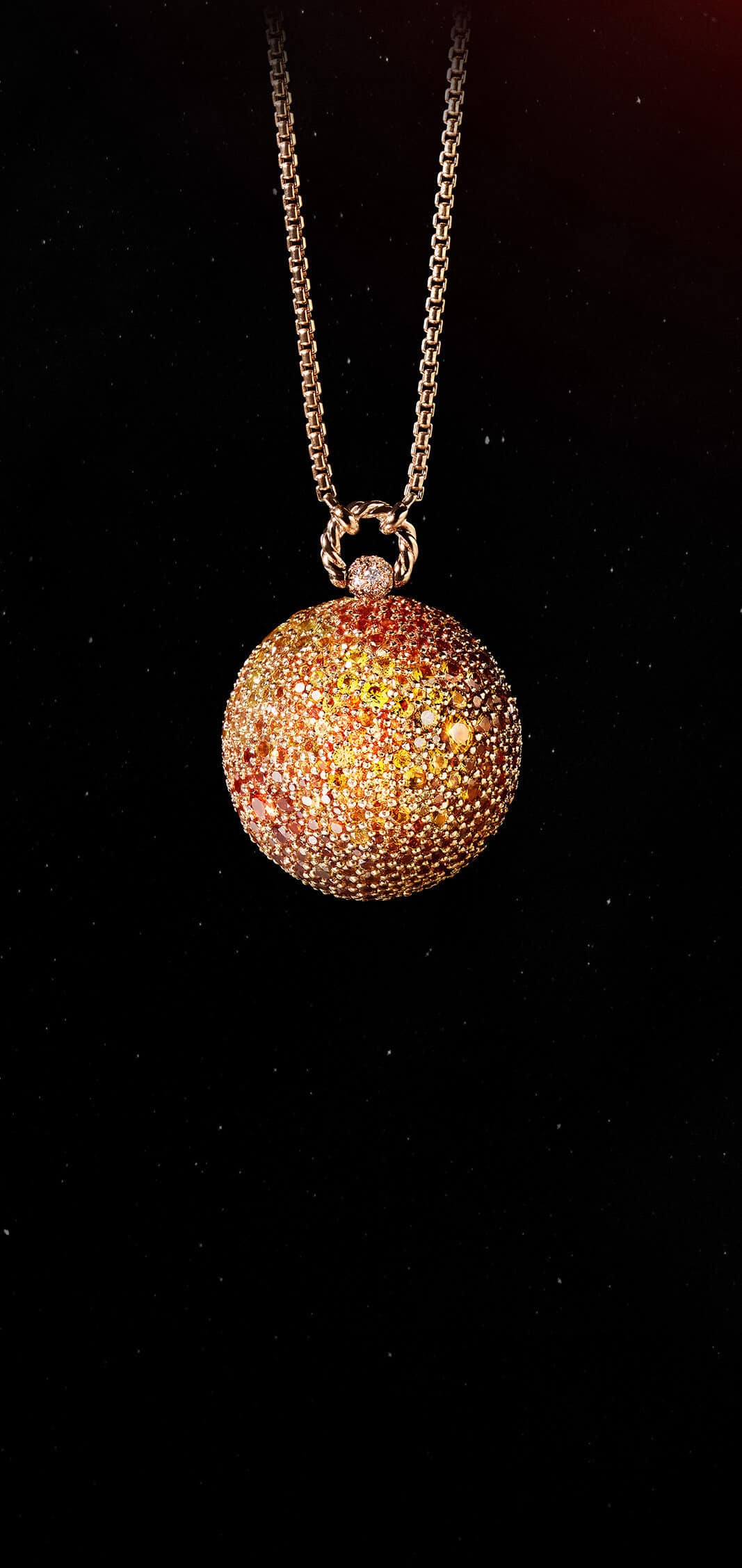 A color photo shows the David Yurman Solari Planet Sun pendant necklace in front of a starry night sky. The pendant is crafted from 18K rose gold with yellow and orange sapphires.