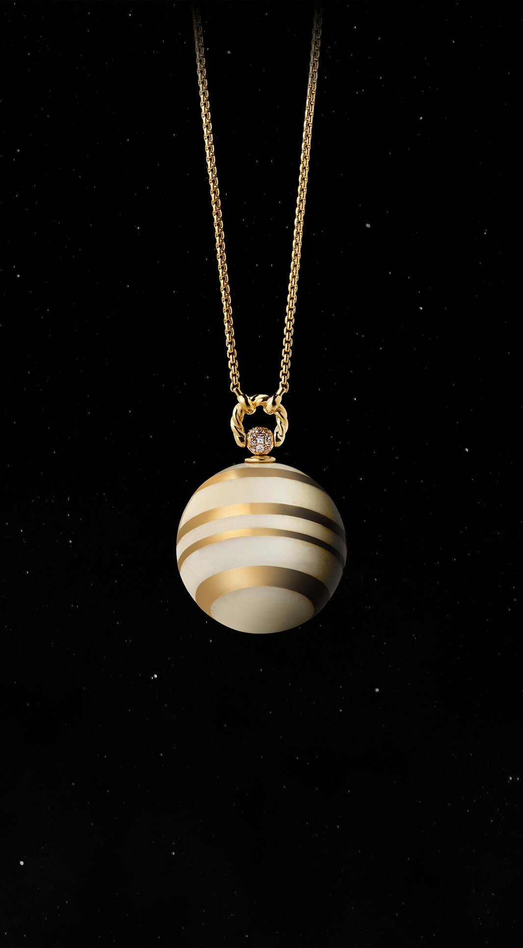 A color photo shows the David Yurman Solari Planet Venus pendant necklace in front of a starry night sky. The pendant is crafted from 18K yellow gold with white jasper and white diamonds.