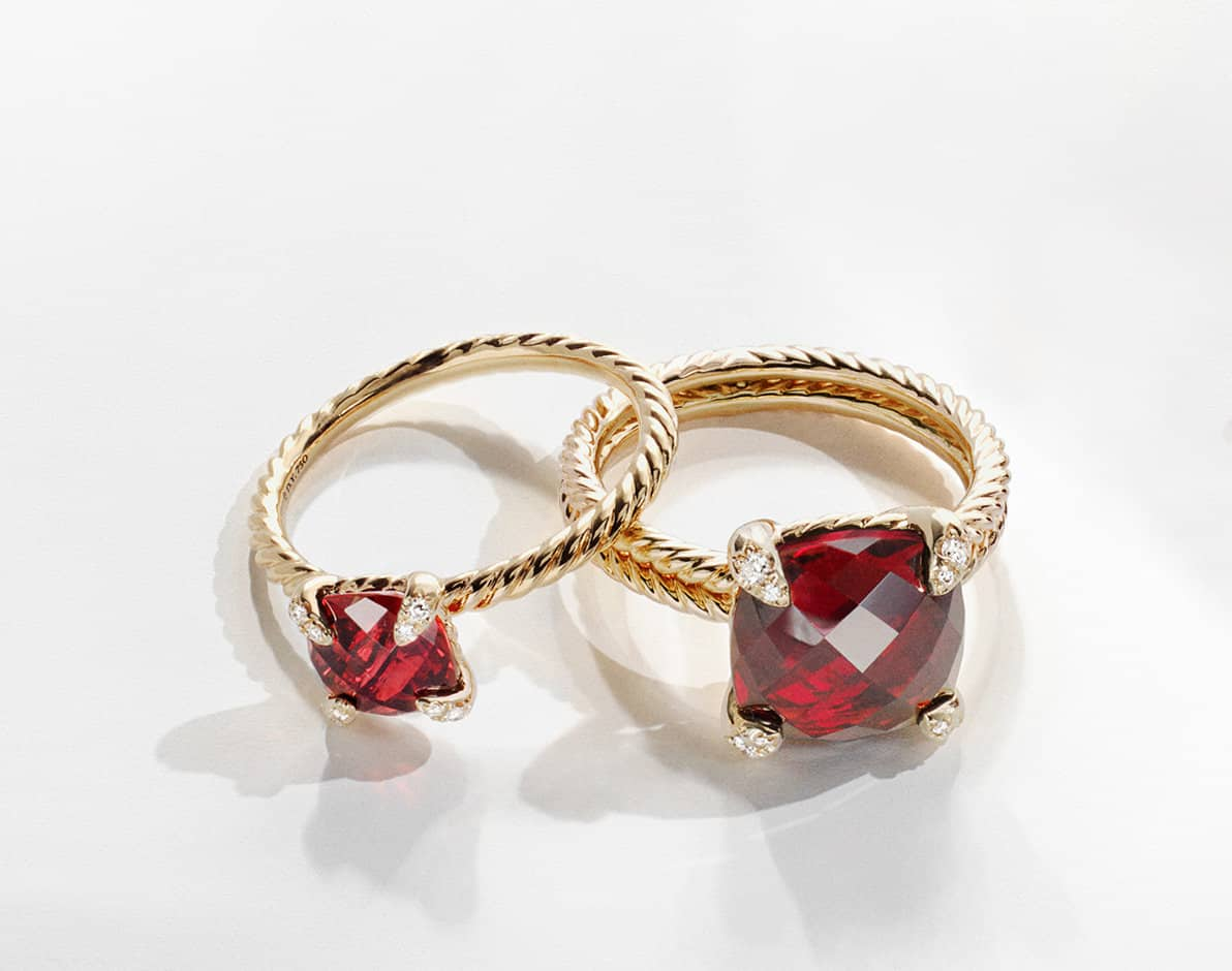 A color photo shows two David Yurman Chatelaine rings of different dimensions, with the smaller ring partially laying over the larger ring and both casting long shadows on top of a white surface. The jewelry is crafted from 18K yellow gold with faceted garnet and white diamonds.