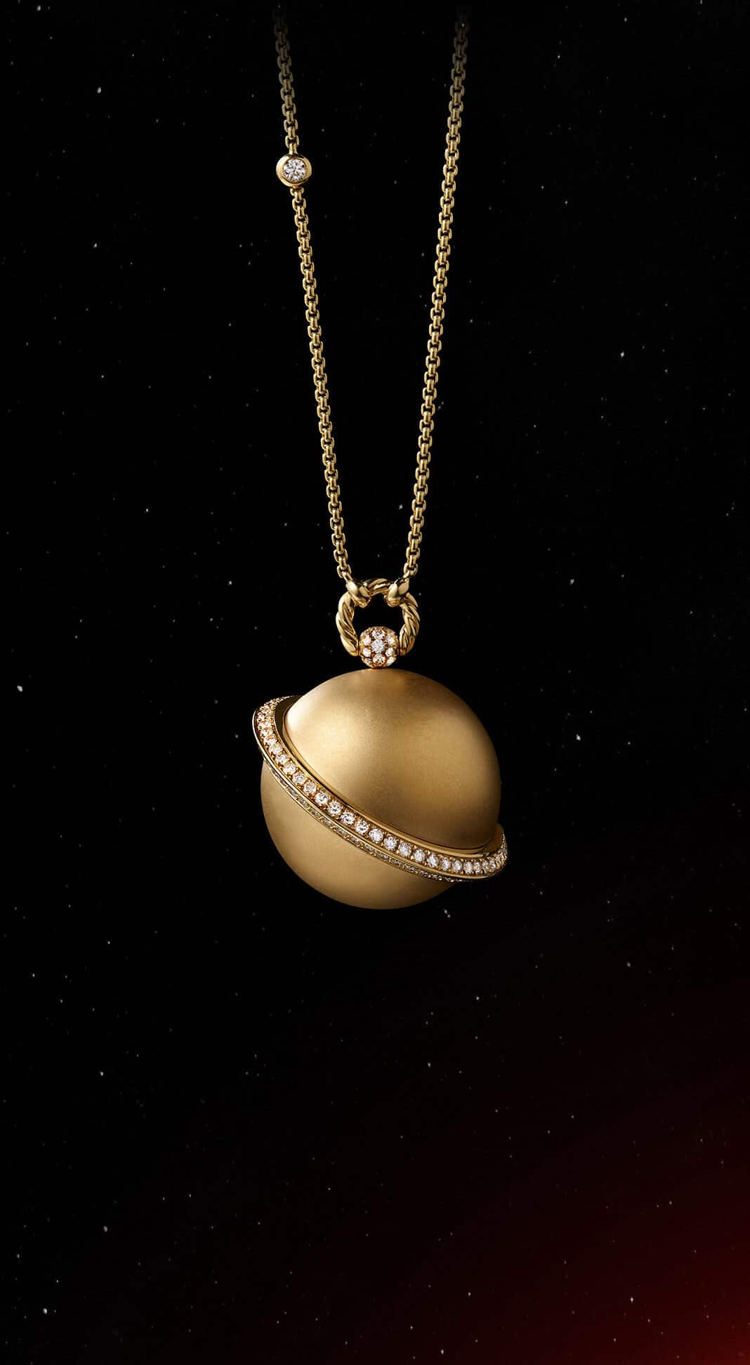 A color photo shows the David Yurman Solari Planet Saturn pendant necklace in front of a starry night sky. The pendant is crafted from 18K yellow gold with white diamonds.