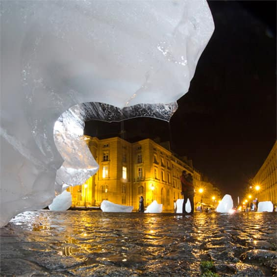 A color photograph of people taking pictures of 'Ice Watch Project,' ice sculptures by Olafur Eliasson and Minik Thorleif Rosing at Place du Pantheon in Paris. A color photograph of artist Ai Weiwei's lion sculptures carved from ice at night at Norrmalmstorg before the Stockholm International Film Festival 2014.