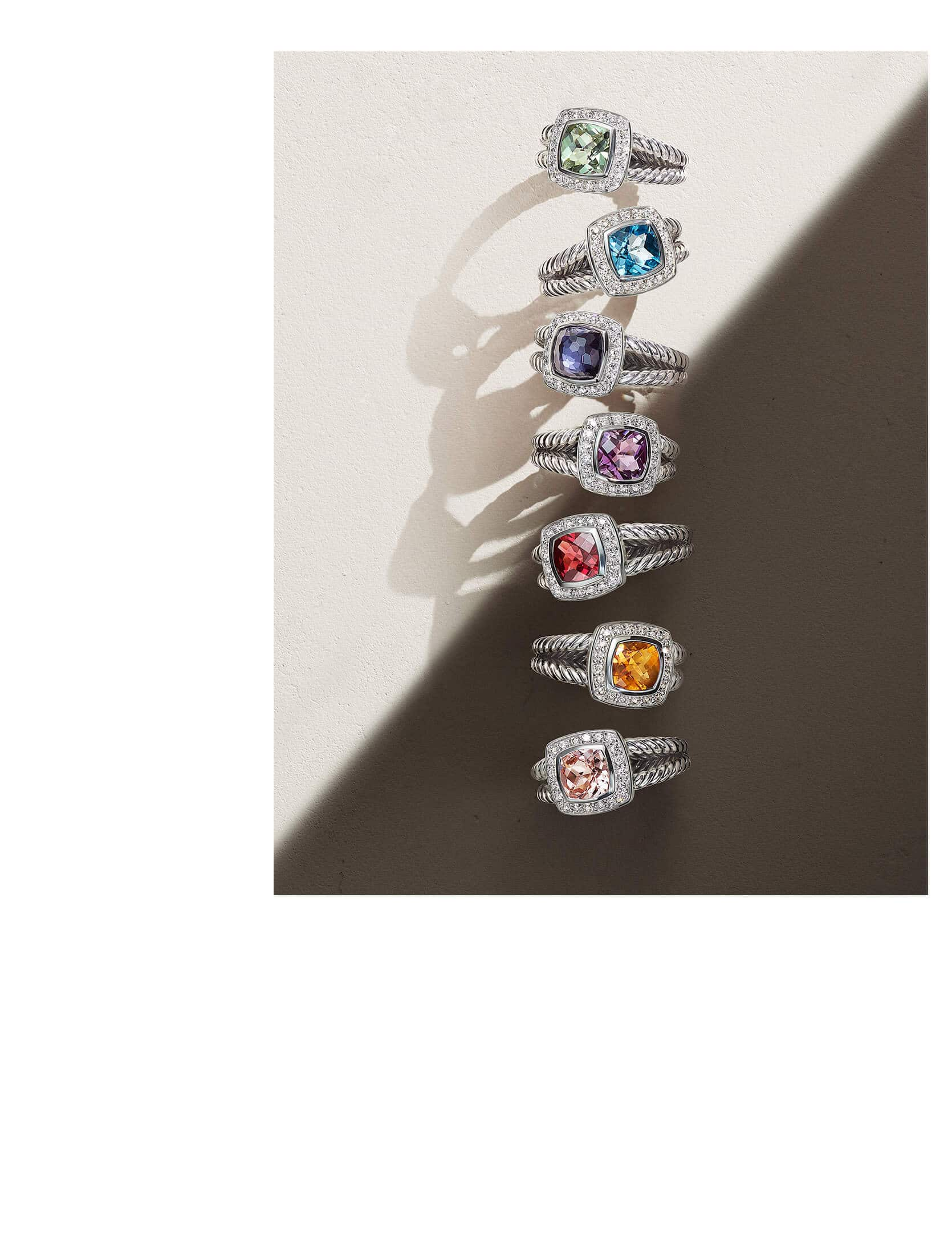 A color photograph shows a vertical row of seven David Yurman Petite Albion rings casting long shadows atop a beige surface cut in half by shadow and light. Each ring crafted from sterling silver with pavé white diamonds and prasiolite, blue topaz, black orchid, amethyst, garnet, citrine or morganite center stones.