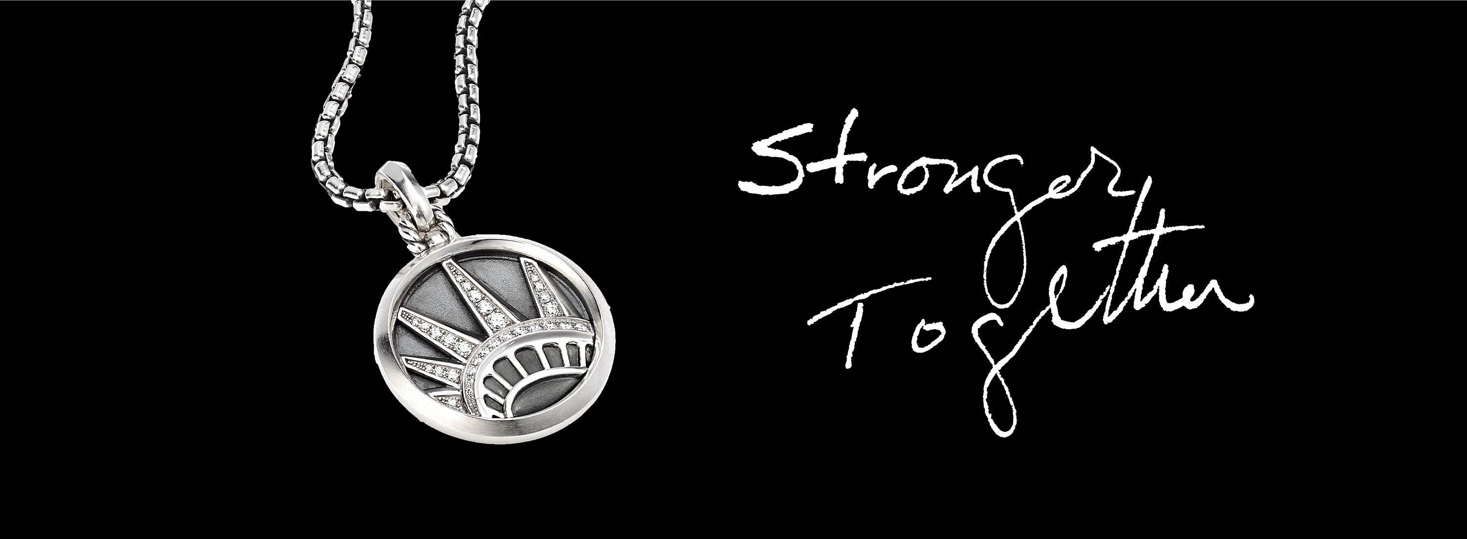 "A color photo shows a David Yurman NYC Statue of Liberty charm strung on a box-chain necklace and laying against a black background next to the words ""Stronger Together"" written by hand. The jewelry is crafted from sterling silver with or without pavé white diamonds."
