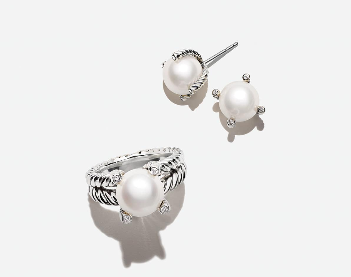 A color photo shows a David Yurman ring and a pair of David Yurman stud earrings arranged in a group casting long shadows on top of a white surface. The jewelry is from the Cable Collectibles collection and is crafted from sterling silver with cultured pearls and white diamonds.